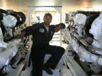 Technician Vanduir Dasilva Stands with Dual MAN 12 Cylinder Marine Diesel Engines